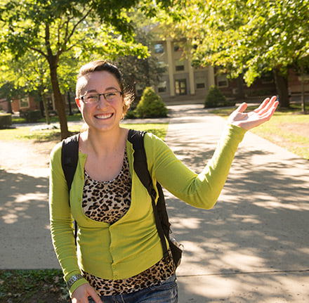 Student waving while walking across the Quad